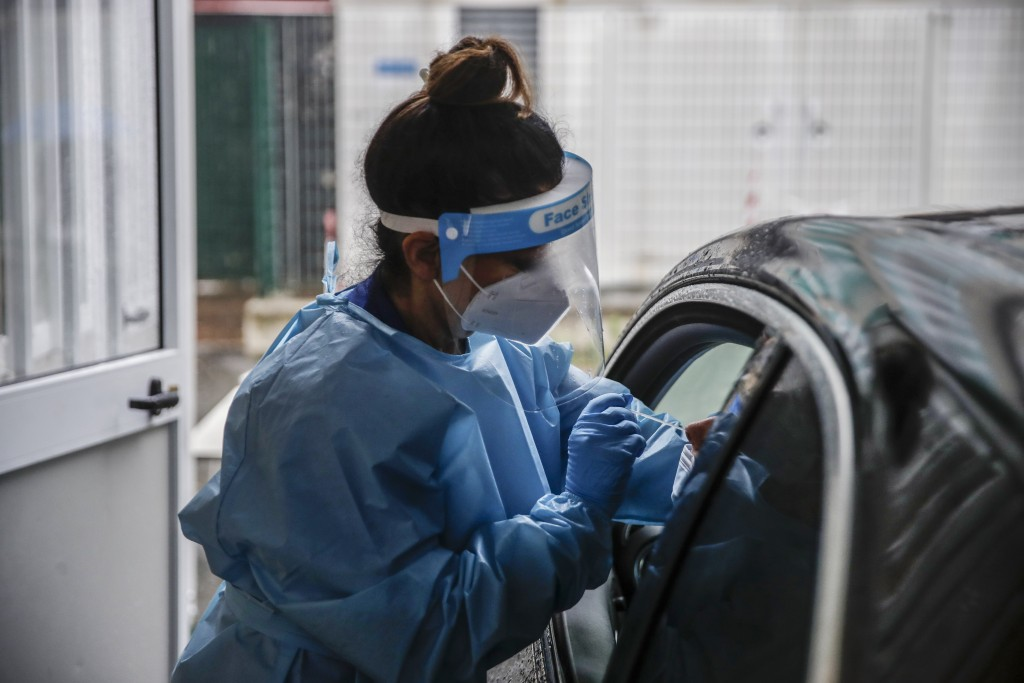 A paramedic takes swabs to test for COVID-19 at a drive-through at the San Paolo hospital, in Milan, Italy, Thursday, Oct. 15, 2020. Coronavirus infec...