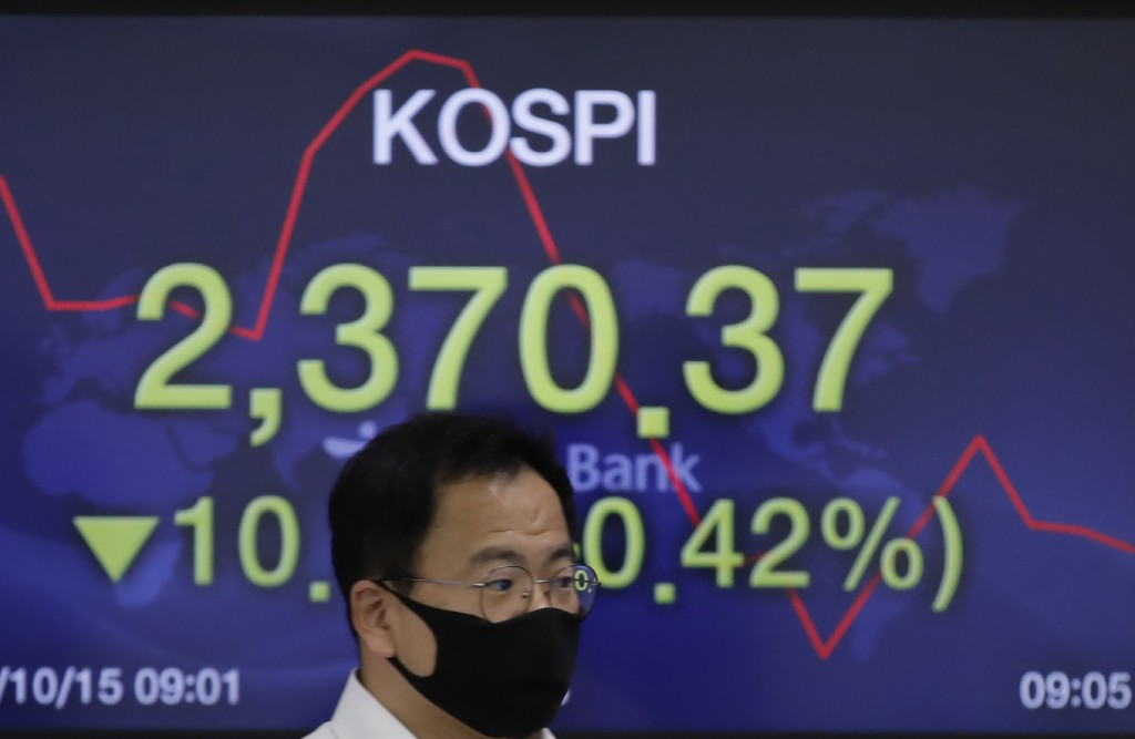 A currency trader walks by a screen showing the Korea Composite Stock Price Index (KOSPI) at the foreign exchange dealing room in Seoul, South Korea, ...