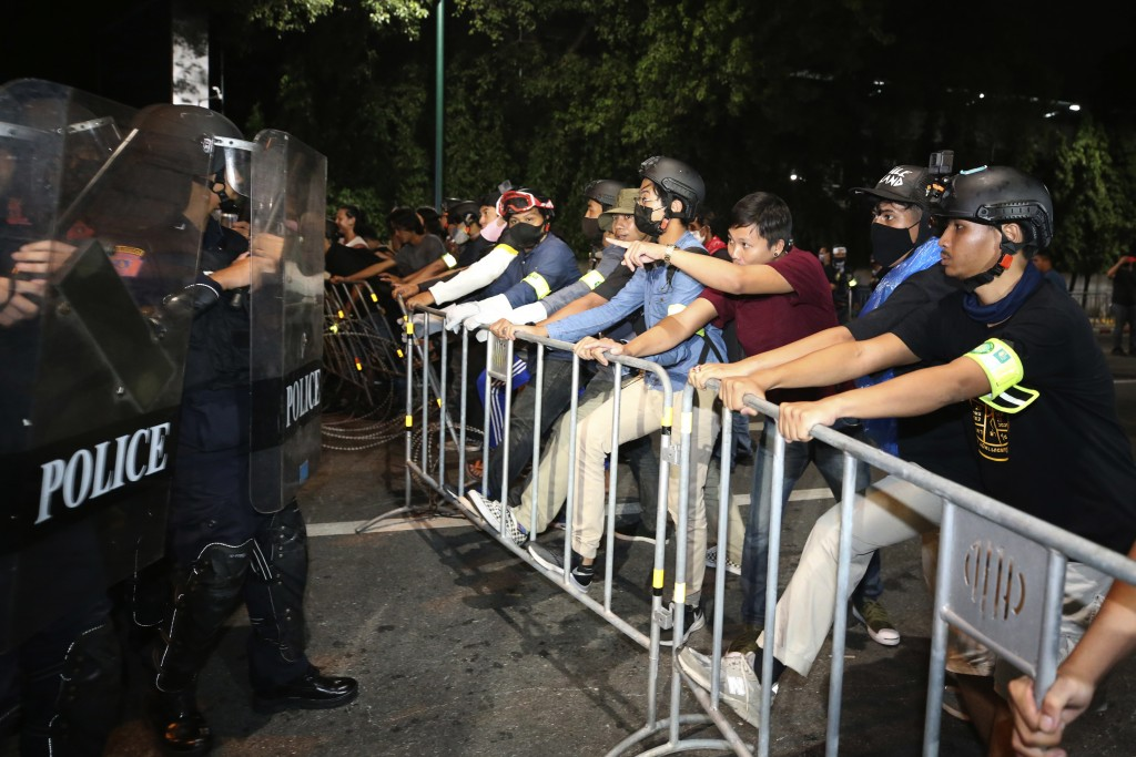 Pro-democracy protesters stand in front of Thai policemen with riot shields during a demonstration in Bangkok, Thailand, Thursday, Oct. 15, 2020. Thai...