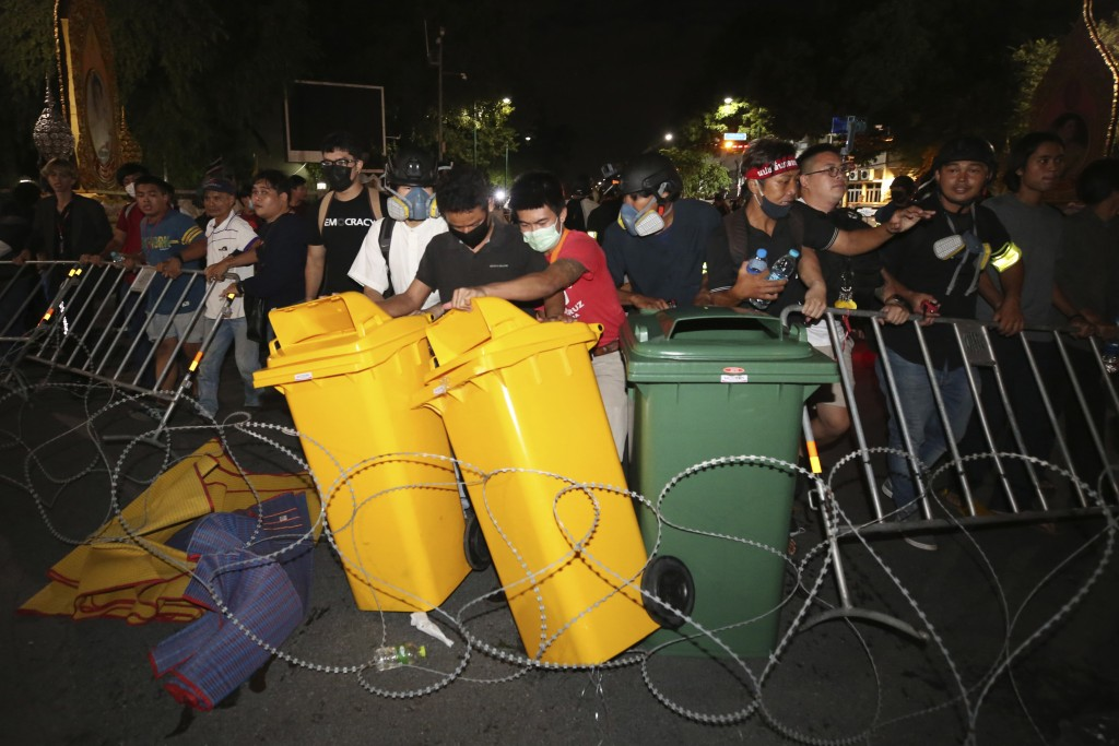 Pro-democracy protesters move trash bins and barriers during a demonstration in Bangkok, Thailand, Thursday, Oct. 15, 2020. Thai police dispersed a gr...