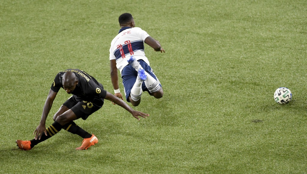 Vancouver Whitecaps forward Cristian Dajome, right, is tripped up by Los Angeles FC forward Bradley Wright-Phillips during the first half of an MLS so...