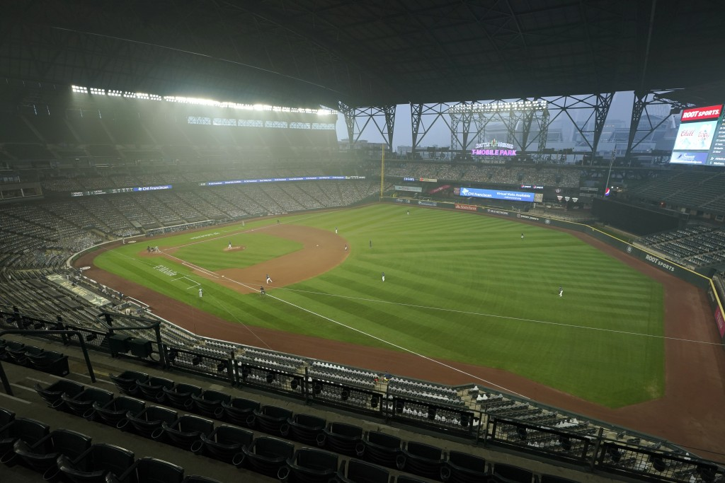 FILE - In this Sept. 14, 2020, file photo, smoke from wildfires in Oregon and California create hazy conditions at T-Mobile Park in Seattle during a b...
