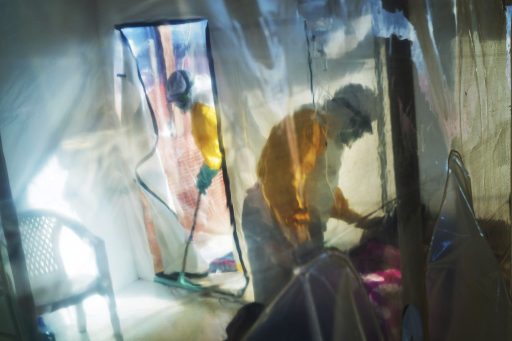 FILE - In this Saturday, July 13, 2019 file photo, health workers wearing protective suits tend to an Ebola victim kept in an isolation tent in Beni, ...