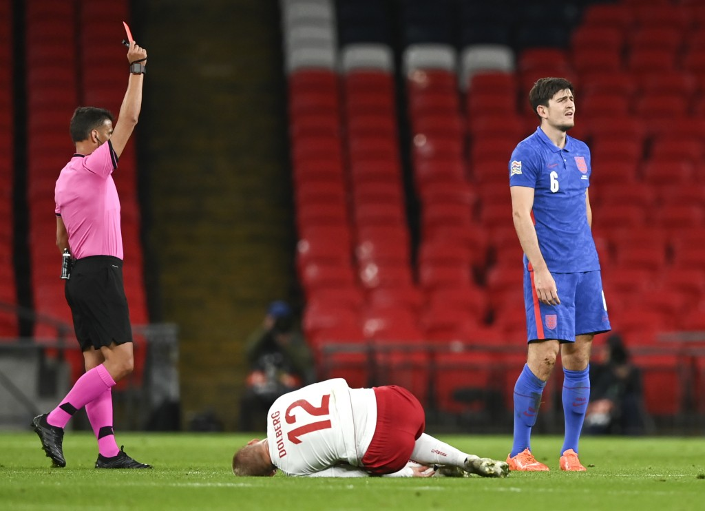 England's Harry Maguire, right, reacts as he is shown a red card by referee Jesus Gil Manzano, left, during the UEFA Nations League soccer match betwe...