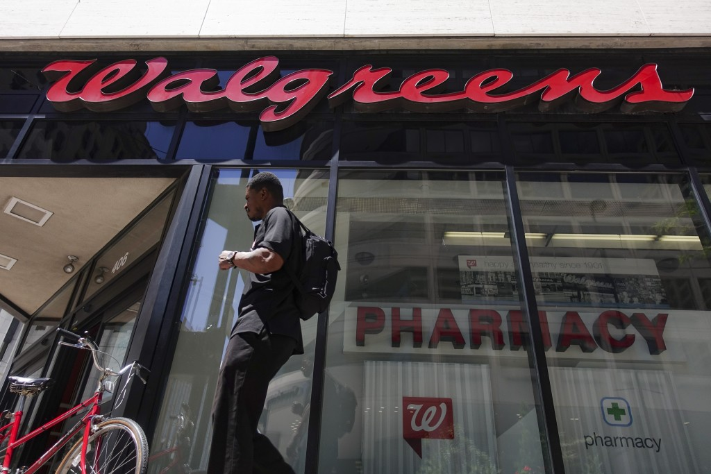 FILE - In this June 25, 2016, file photo a person walks by signage hangs outside a Walgreens pharmacy in downtown Cincinnati.  COVID-19 took another b...