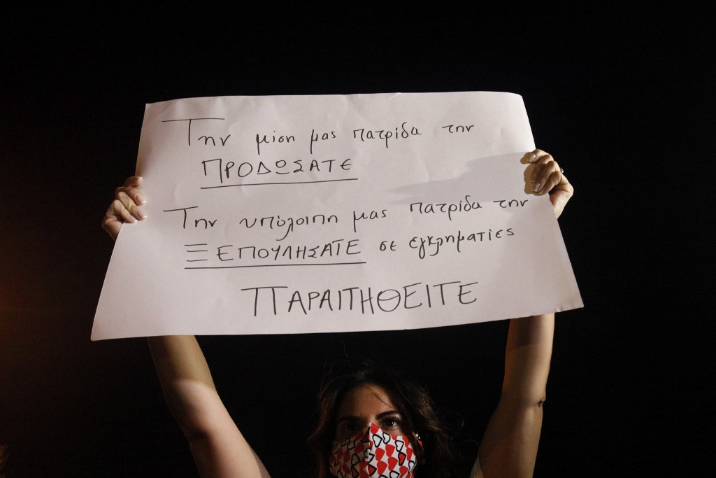 "A protester holds up a placard reading in Greek ""You betrayed half of our country, the rest you sold out to criminals. Resign"" during a demonstration ..."