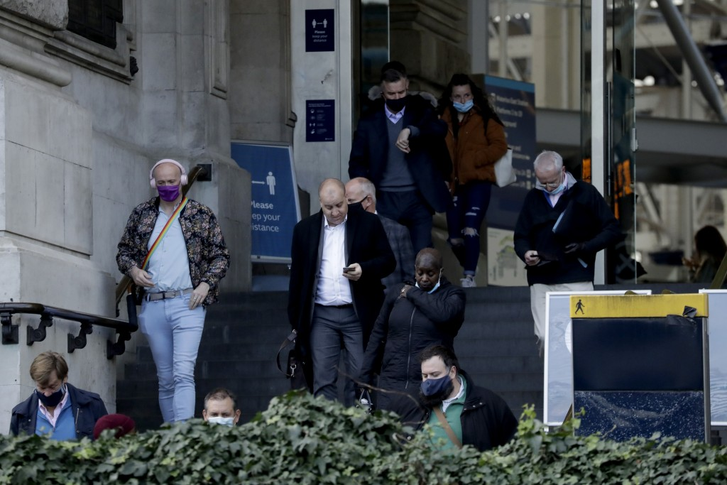 People walk down the steps of the main entrance of Waterloo train station at which point they are allowed to remove their face coverings, in London, T...