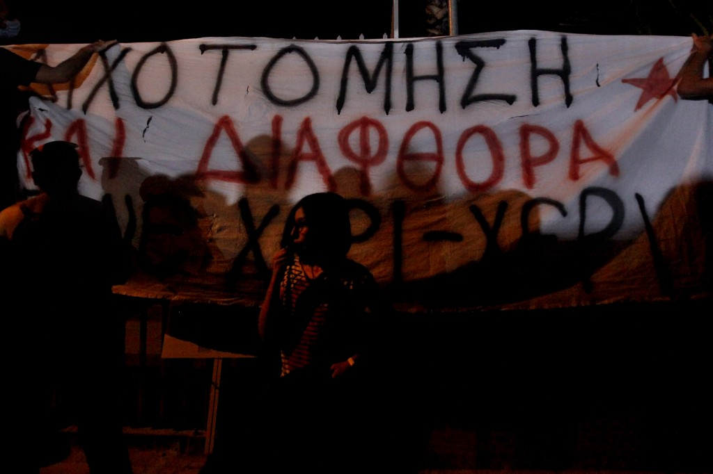 "A protestor stands in front of a banner reading in Greek ""Division and Corruption hand in hand"" during a demonstration against corruption outside of t..."