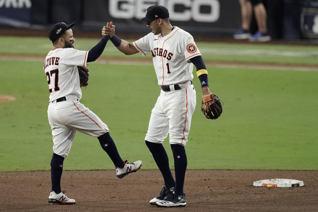 Houston Astros' Jose Altuve celebrates with Carlos Correa (1) after Game 4 of a baseball American League Championship Series against the Tampa Bay Ray...
