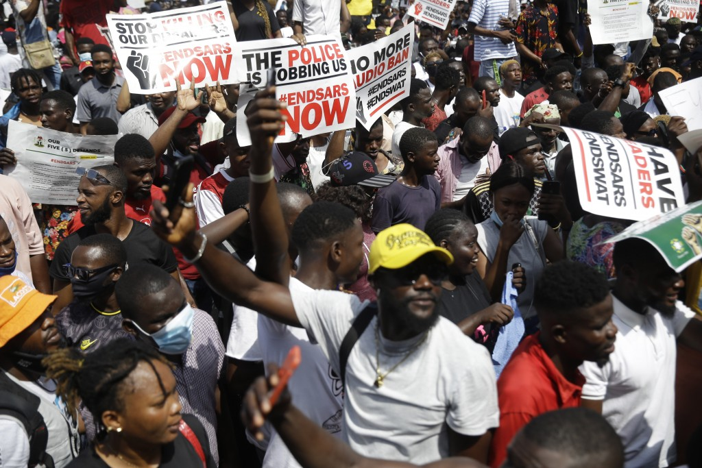 People hold banners as they demonstrate on the street to protest against police brutality in Lagos, Nigeria, Thursday Oct. 15, 2020. Protests against ...