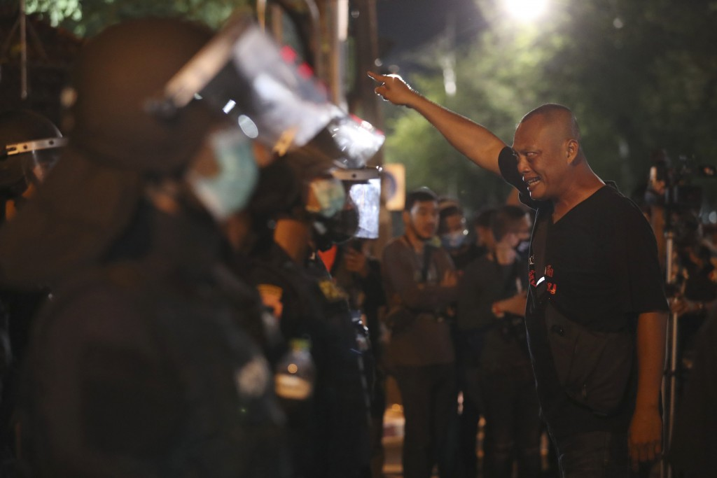 A pro-democracy protester shouts at Thai policemen during a demonstration in Bangkok, Thailand, Thursday, Oct. 15, 2020. Thai police dispersed a group...
