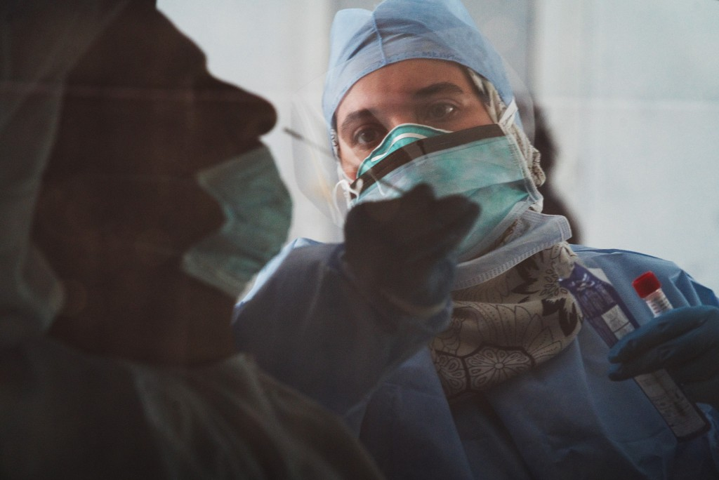 FILE - In this April 2, 2020, photo taken through a tinted car window, a technician takes a nasal swab for a new coronavirus detection test at a drive...