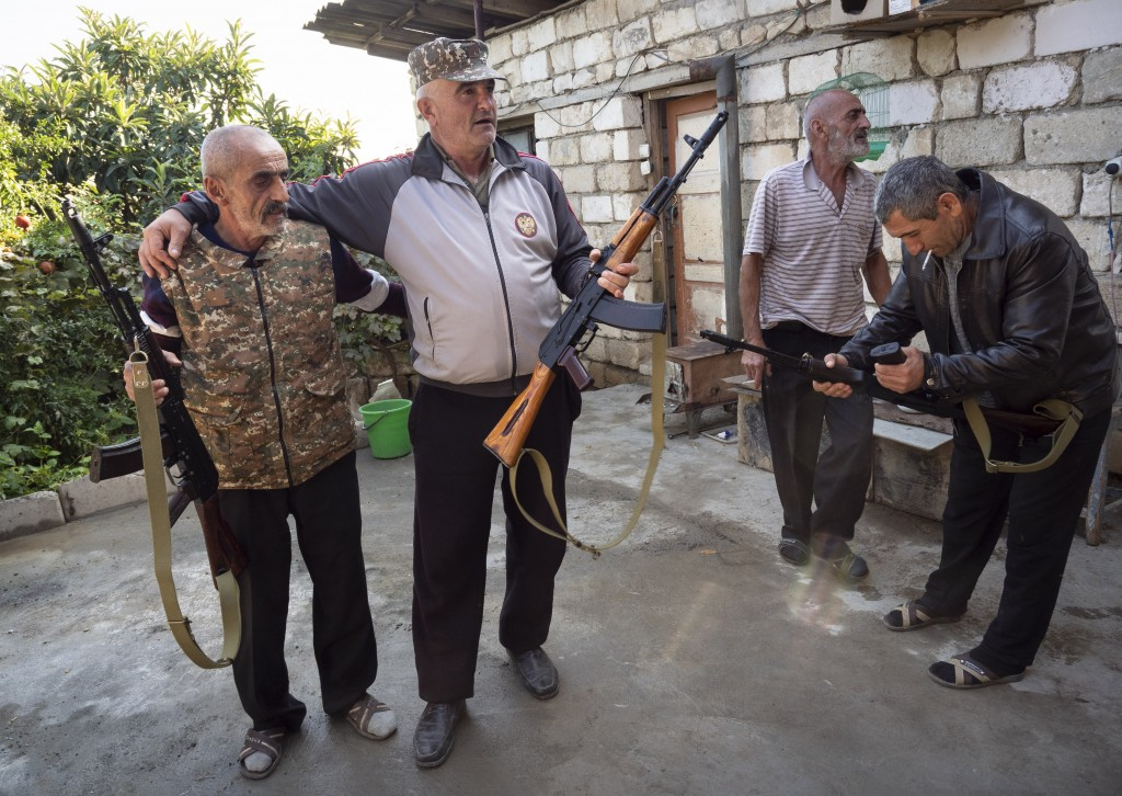 Local residents hold Kalashnikov guns that they received from a recruitment office in the town of Martuni, the separatist region of Nagorno-Karabakh, ...