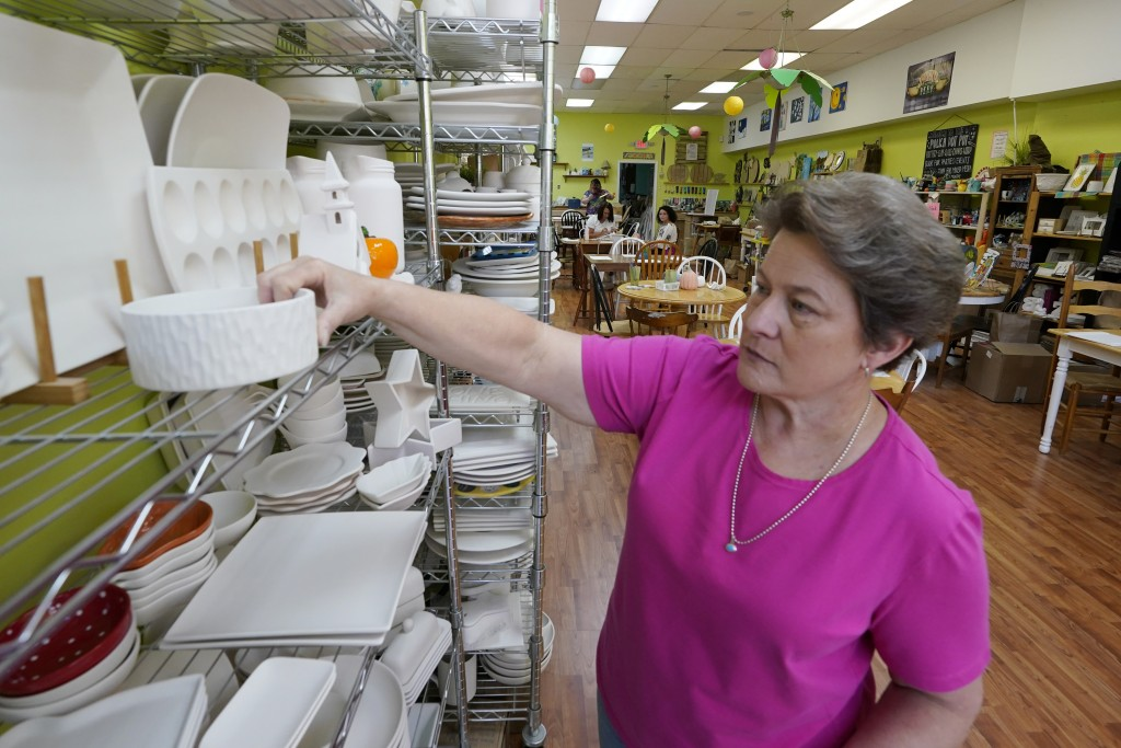 Polka Dot Pot owner Emily Rhodes, arranges merchandise in her shop in the Old Town area Wednesday Oct. 7, 2020, in Winchester, Va.   The viral pandemi...