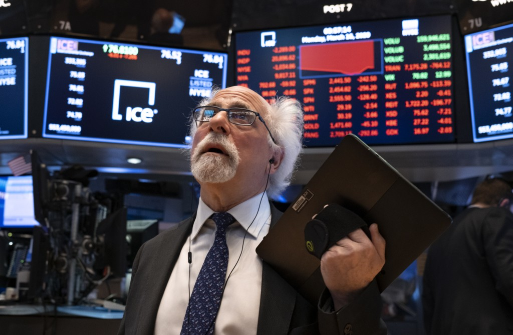 FILE - In this Monday, March 16, 2020, file photo, trader Peter Tuchman works on the floor of the New York Stock Exchange.  The 2020 presidential elec...