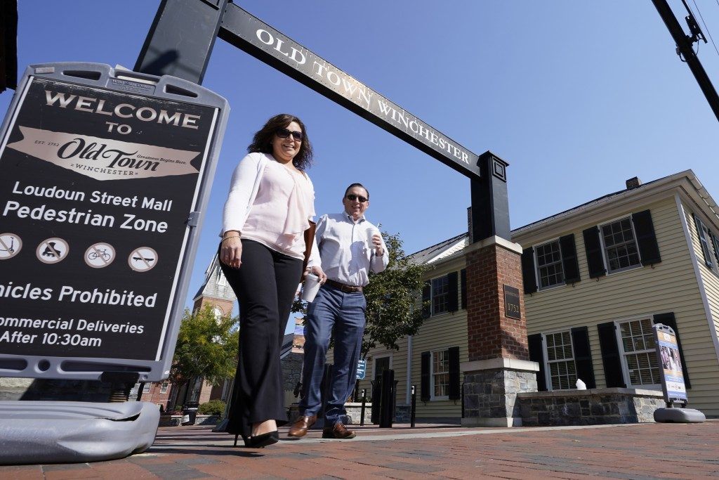 Pedestrians walk along the downtown mall area Wednesday Oct. 7, 2020, in Winchester, Va.  The viral pandemic has hammered small businesses across the ...