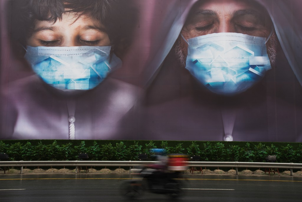 FILE - In this Wednesday, April 15, 2020 file photo, a motorcycle delivery man rides past a billboard urging people to stay home over the coronavirus ...