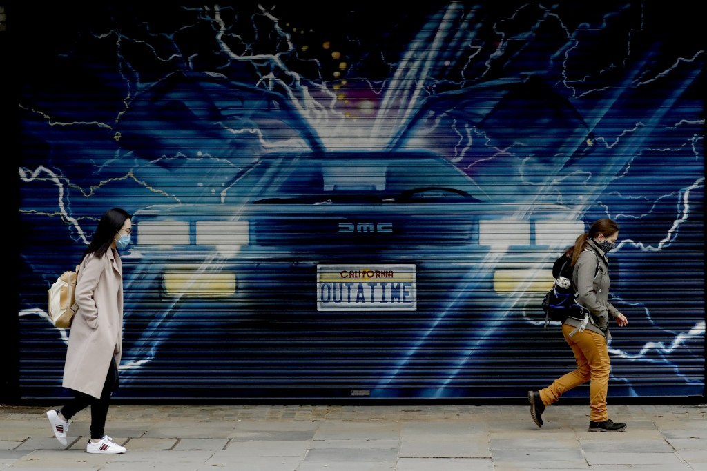 """People wearing face masks to try to curb the spread of coronavirus walk past an image for """"Back to the Future the Musical"""" on a shutter outside the Ad..."""
