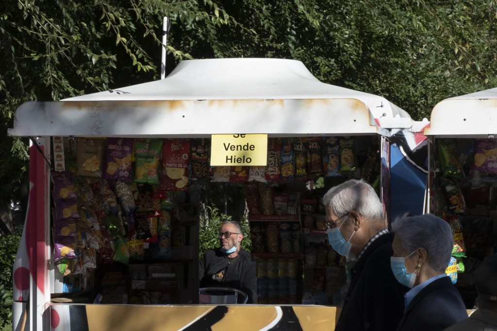 A couple wearing face masks to protect against the spread of coronavirus walk past a kiosk advertising ice for sale alongside drinks and snacks in Mad...
