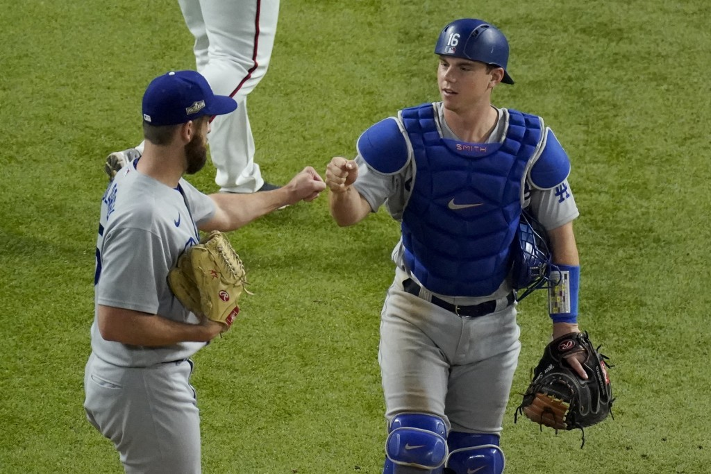 Los Angeles Dodgers relief pitcher Adam Kolarek, left, and catcher Will Smith celebrate their win against the Atlanta Braves in Game 3 of a baseball N...
