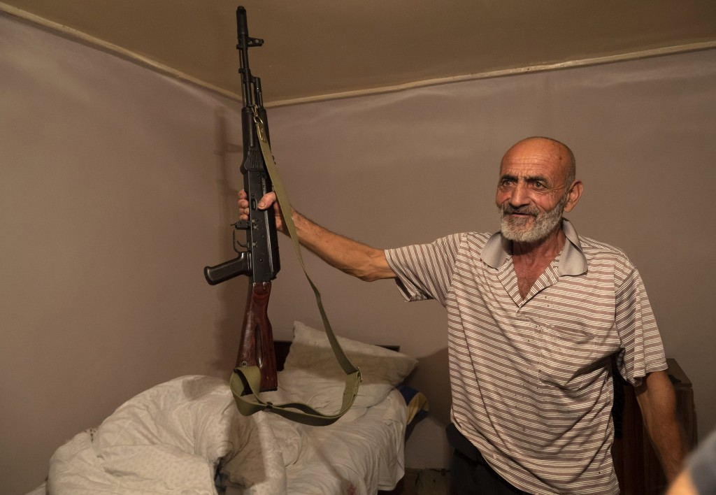 Local resident, Yury Ovanisyan holds a Kalashnikov guns that he received from a recruitment office in the town of Martuni, the separatist region of Na...