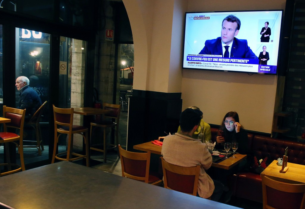 People dine at a restaurant as France's President Emmanuel Macron gives an address on television, in Saint jean de Luz, southwestern France, Wednesday...