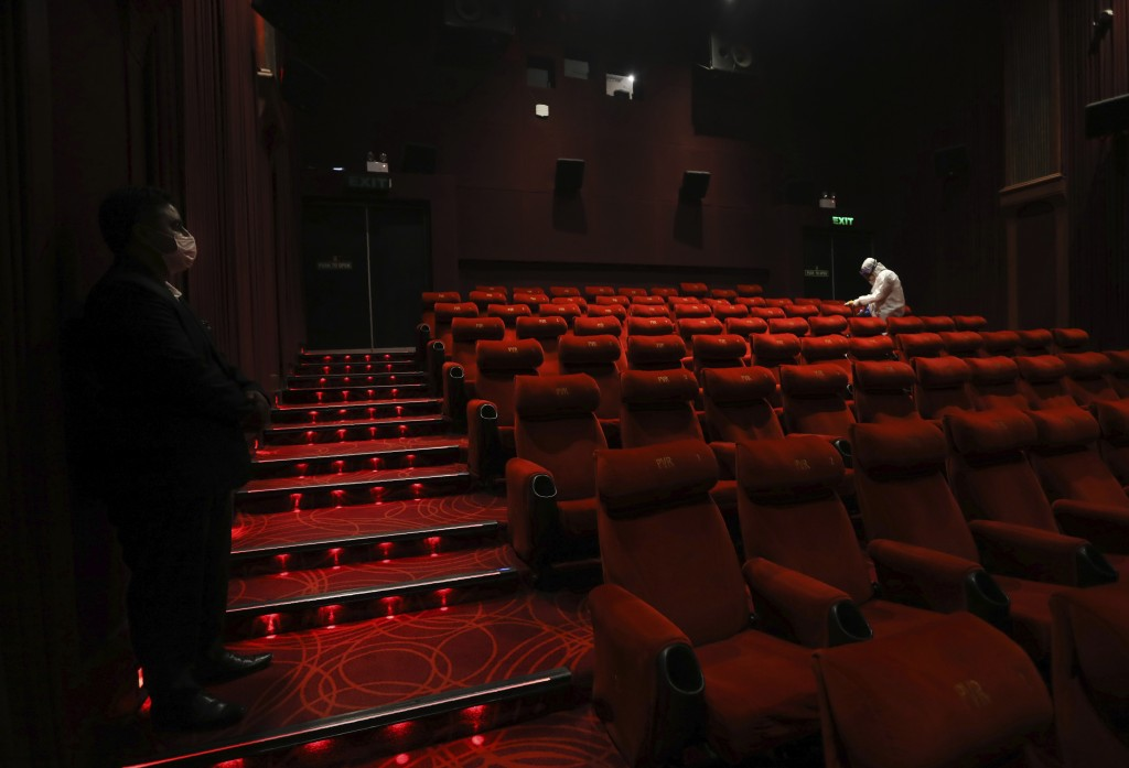 FILE - In this Friday, July 31, 2020, file photo, a worker of PVR cinemas, a multiplex cinema chain, sanitizes a theater during a press preview to sho...