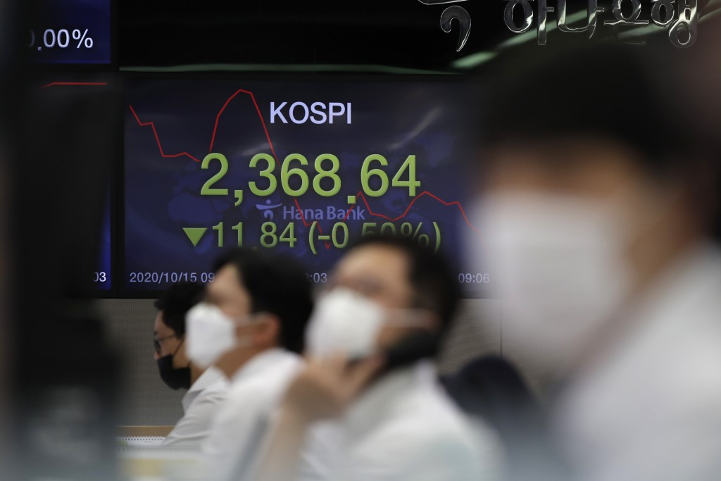 Currency traders watch computer monitors near a screen showing the Korea Composite Stock Price Index (KOSPI) at the foreign exchange dealing room in S...