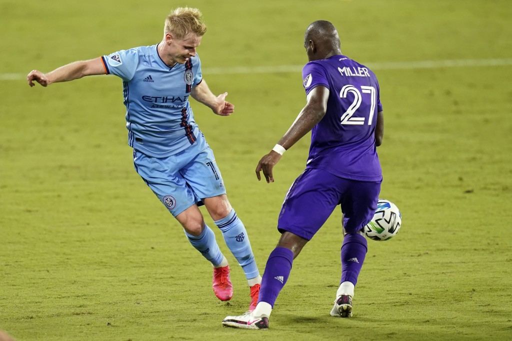 New York City FC midfielder Gary Mackay-Steven, left, passes the ball around Orlando City defender Kamal Miller (27) during the second half of an MLS ...