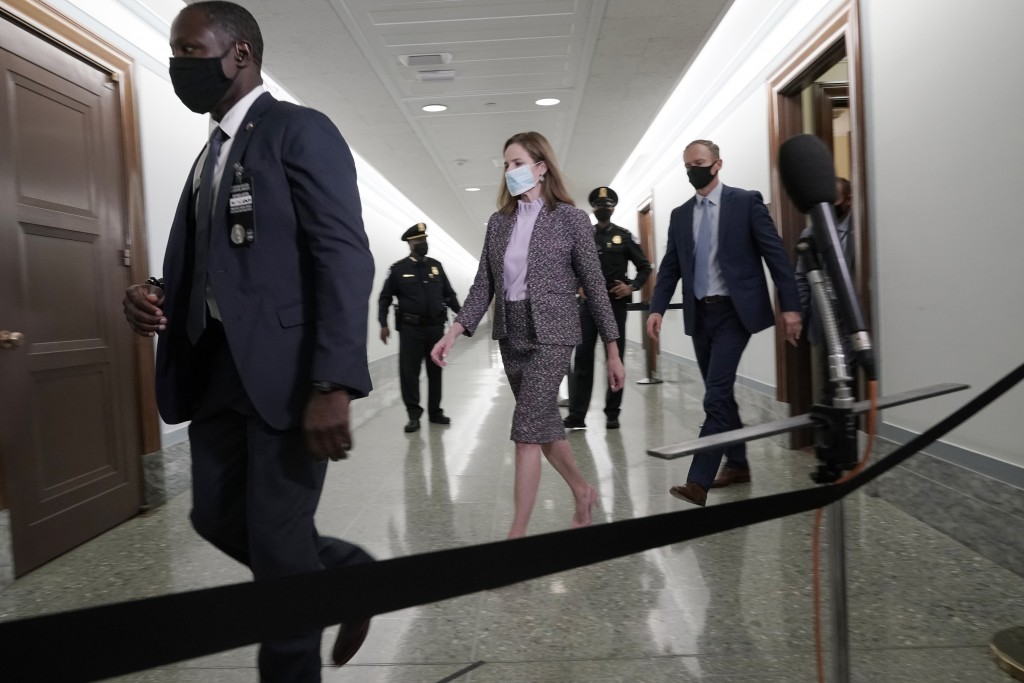 Supreme Court nominee Amy Coney Barrett and her husband Jesse, right, arrive after a break to her confirmation hearing before the Senate Judiciary Com...