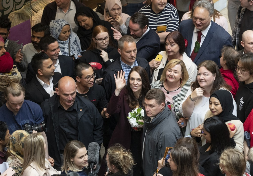 New Zealand Prime Minister Jacinda Ardern, center, waves as she arrives at a shopping mall in Christchurch, New Zealand, Wednesday, Oct. 14, 2020. Opi...