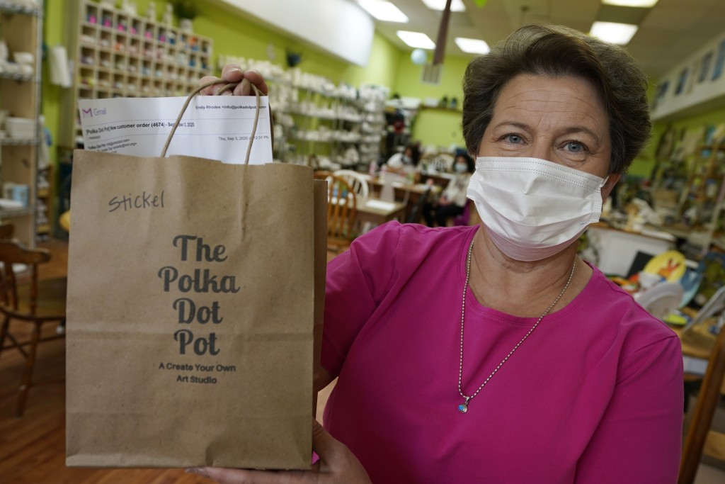 Polka Dot Pot owner Emily Rhodes holds a take home bag at her shop in the Old Town area Wednesday Oct. 7, 2020, in Winchester, Va.  The viral pandemic...