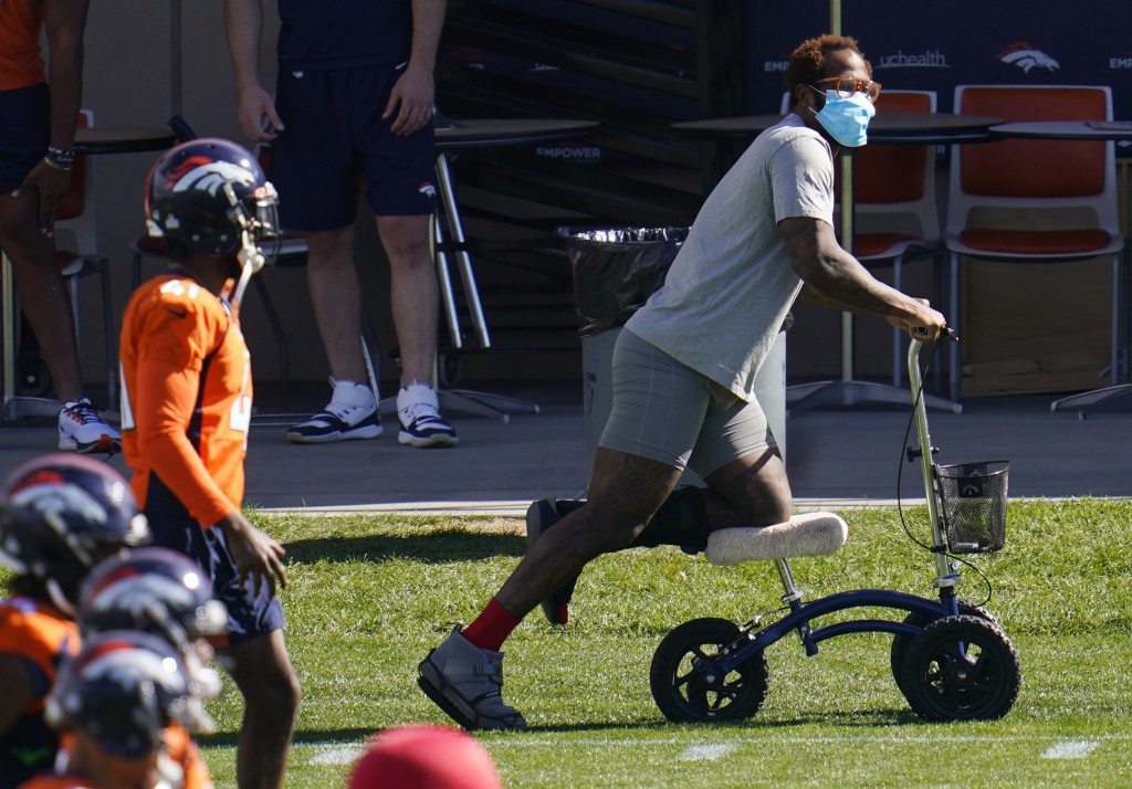 Injured Denver Broncos outside linebacker Von Miller uses a scooter to maneuver around as his teammates warm up before taking part in drills during an...