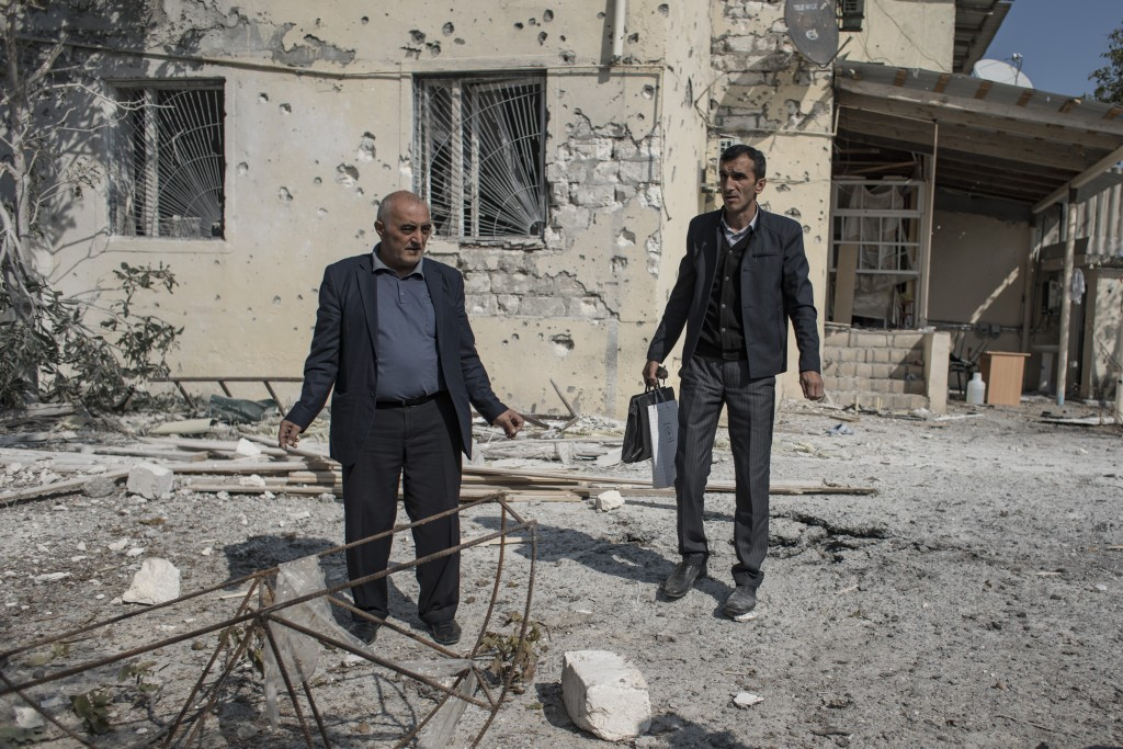 People inspect the damage following overnight shelling by Armenian forces, in the city of Terter, Azerbaijan, Thursday, Oct. 15, 2020. The conflict be...