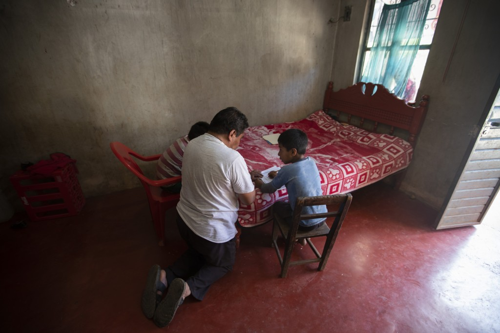 Using a bed as a desk, Agustin Vazquez helps his sons Samuel and Hector with their schoolwork handed out by teachers amid the new coronavirus pandemic...