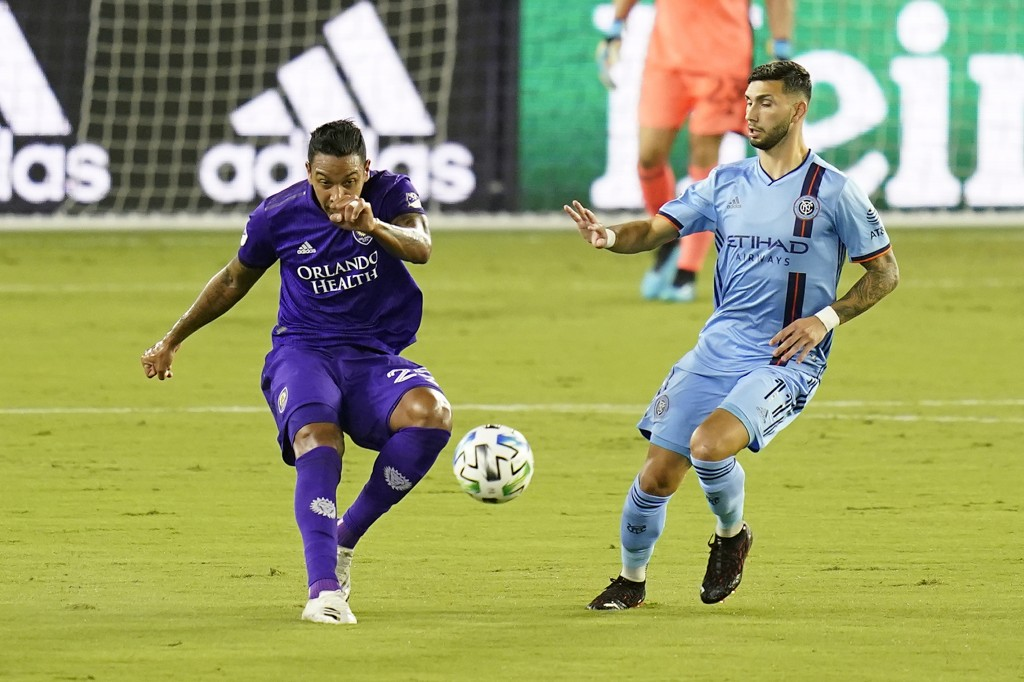 Orlando City midfielder Andres Perea, left, clears the ball past New York City FC midfielder Valentin Castellanos during the first half of an MLS socc...