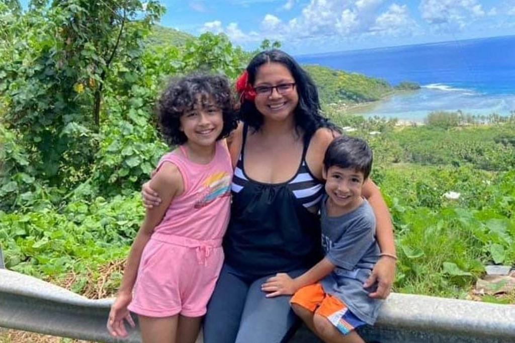 This undated photo, provided by Epifania Rapozo, center, shows her with her two children Mila, left, and Levi, right, on hill side overlooking a sceni...