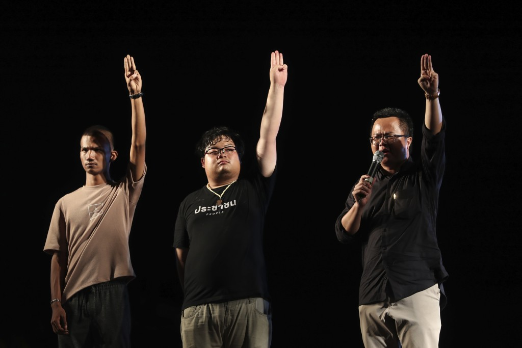 Pro-democracy activists, from left, Panupong Jadnok, Arnon Nampha, Parit Chiwarak, raise three-finger salutes, a symbol of resistance, during a protes...