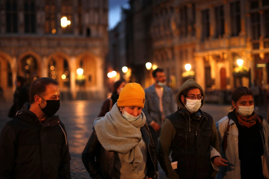 Passers-by, wearing face masks to prevent the spread of coronavirus, walk along the Grande Place or Grand Square in downtown Brussels, Wednesday, Oct....