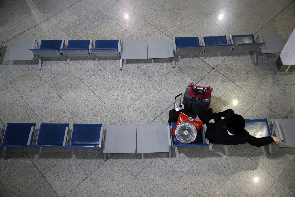 A passenger sits at the empty Eleftherios Venizelos International Airport during a 24-hour strike in public sector in Athens, Thursday, Oct. 15. 2020....