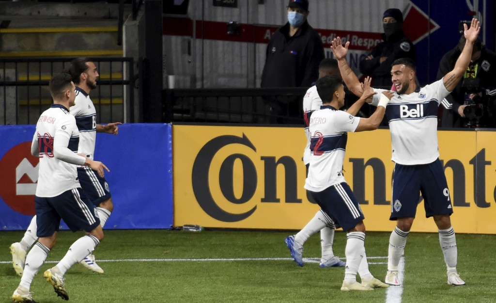 Vancouver Whitecaps forward Lucas Cavallini, right, celebrates with his teammates after scoring a goal during the first half of an MLS soccer match ag...
