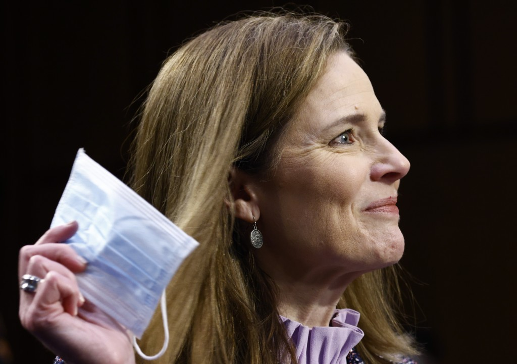 Supreme Court nominee Amy Coney Barrett holds a face mask up as she testifies during the third day of her confirmation hearings before the Senate Judi...