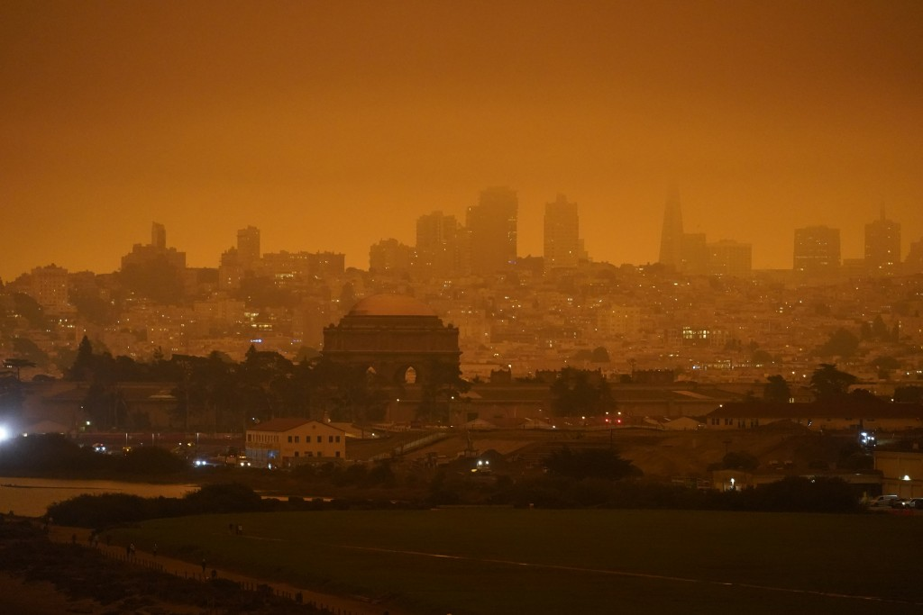 FILE - In this Sept. 9, 2020, file photo, taken at 11:18 a.m., is a dark orange sky above Crissy Field and the city caused by heavy smoke from wildfir...