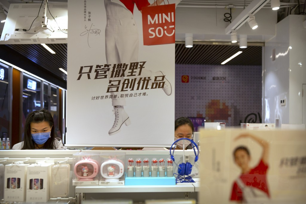 Customers wearing face masks to protect against the coronavirus browse at a Miniso shop at a shopping mall in Beijing, Thursday, Oct. 15, 2020.  Minis...