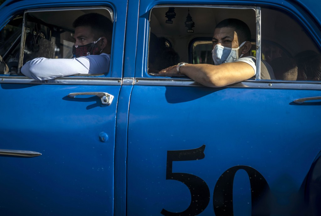 Wearing masks as a precaution against the spread of the new coronavirus people travel in a taxi in Havana, Cuba, Wednesday, Oct. 14, 2020. (AP Photo /...