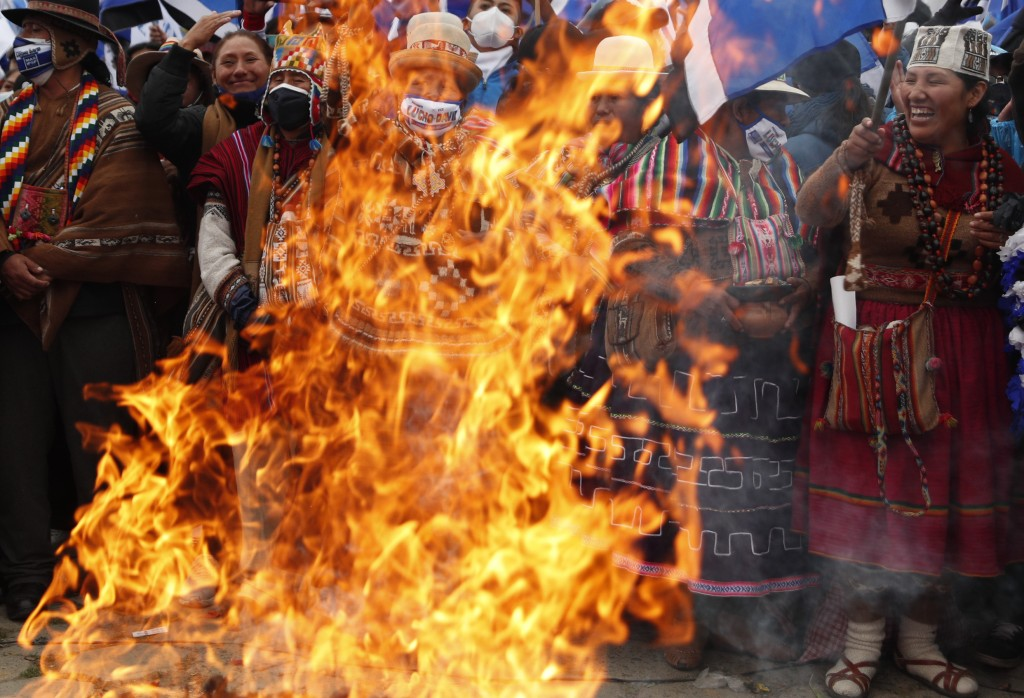 """Supporters of presidential candidate Luis Arce from the Movement Towards Socialism Party, MAS, burn an offering to the """"Pachamama,"""" or Mother Earth du..."""
