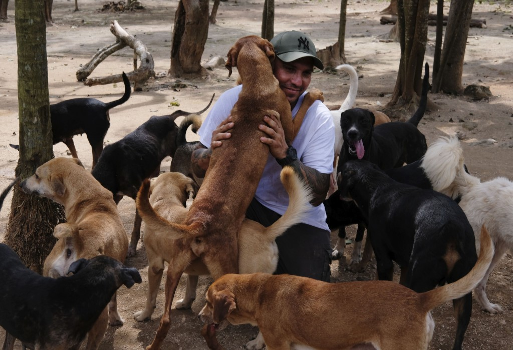 In this Oct. 13, 2020, photo, Ricardo Pimentel is greeted by dogs that he rescued at his Tierra de Animales (Land of Animals) shelter in Leona Vicario...