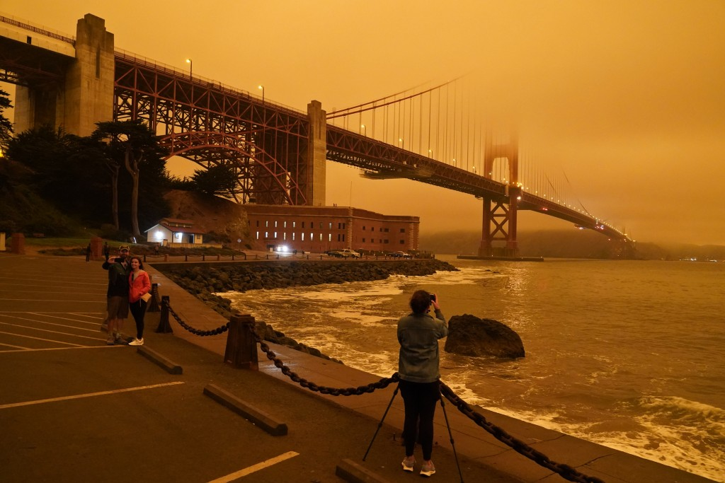 FILE - In this Sept. 9, 2020, file photo, taken at 11:25 a.m. people stop near Fort Point to take pictures of an orange sky over the Golden Gate Bridg...