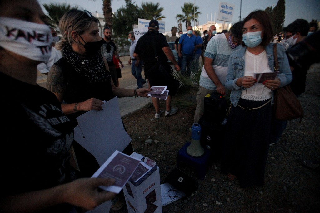 Protesters mock copies of Cyprus passports during a demonstration against corruption at a conference center in the capital Nicosia, Cyprus, Wednesday,...