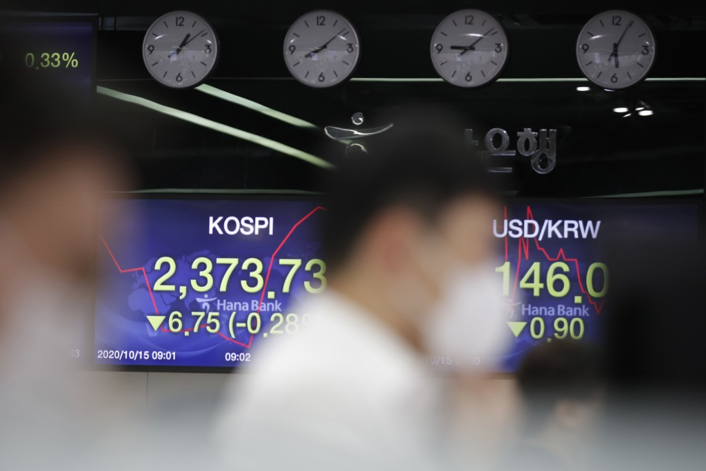 Currency traders watch computer monitors near screens showing the Korea Composite Stock Price Index (KOSPI), left, and the foreign exchange rate betwe...